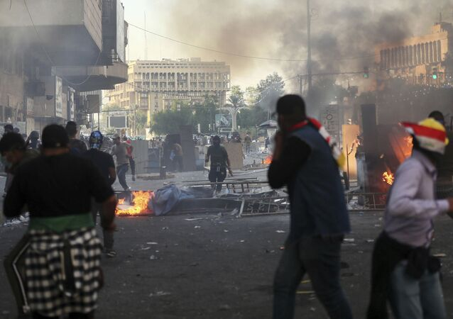 Anti-government protesters set fire and close streets during ongoing protests in Baghdad, Iraq, in central Baghdad, Iraq, Saturday, Nov. 9, 2019.  Mass protests erupted in Baghdad and across southern Iraq last month, calling for the overhaul of the political system established after the 2003 U.S.-led invasion