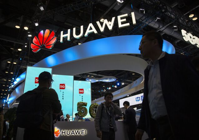 Attendees walk past a display for 5G services from the Chinese technology firm Huawei at the PT Expo in Beijing, Thursday, 31 October 2019