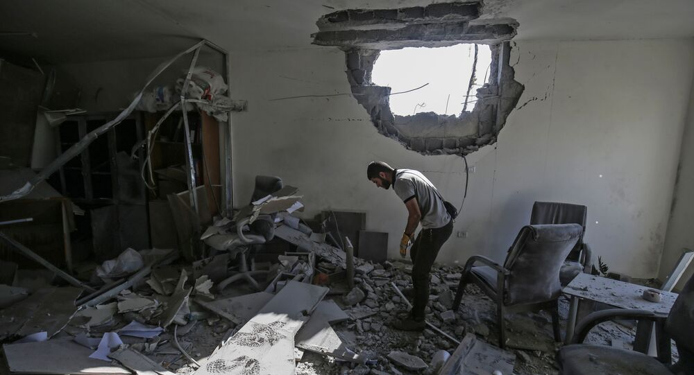 A Palestinian man inspects a damaged building in Gaza City on November 12, 2019