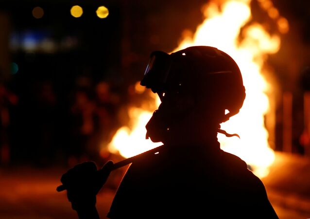 A protester is seen in front of a fire in the Mong Kok area in Hong Kong