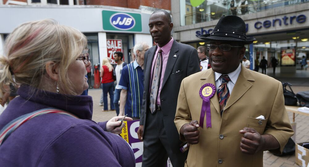 Candidate for the euro-sceptic United Kingdom Independence Party Winston McKenzie, right, speaks to a woman as UKIP supporters campaign for the European and local elections in Croydon, south London, Tuesday, May 20, 2014