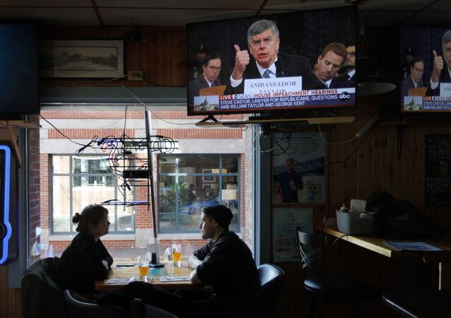 The televised impeachment hearings on monitors at the Commercial Street Pub in Portland, Maine
