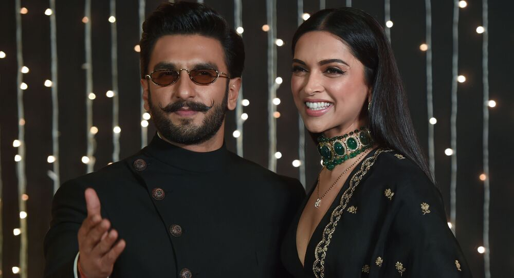 Indian Bollywood actors Ranveer Singh (L) and Deepika Padukone (R) pose as they arrive to attend a wedding reception of a Bollywood actress in Mumbai, India, on December 20, 2018.