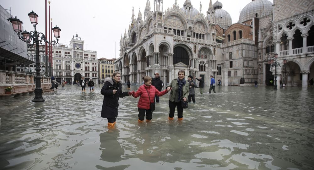 People wade through water in a flooded St. Mark's Square in Venice, Italy, Wednesday, Nov. 13, 2019