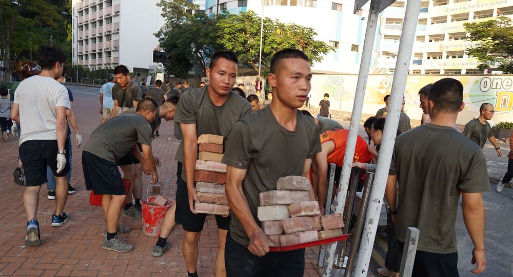 Personnel from the Chinese People's Liberation Army barracks in Hong Kong emerged on to the city streets on November 16, 2019, to help the clean-up after a week of violence and disruption caused by pro-democracy protesters. - In a rare and highly symbolic movement by a garrison which is confined to the barracks under Hong Kong's mini-constitution, scores of men with crewcuts and identical gym kits conducted a lightning-quick removal of bricks and debris near their base.