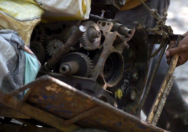 A Venezuelan man carries scrap metal to sell