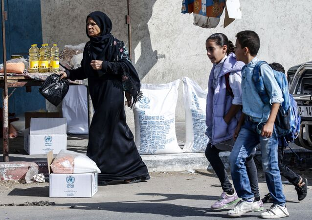 Palestinian pupils walk by a women receiving food aid from a United Nations Relief and Works Agency (UNRWA) distribution centre in the southern Gaza Strip refugee camp of Rafah, on November 17, 2019.