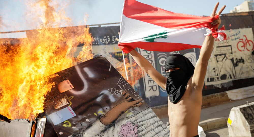 A masked protester holding a Lebanese flag walks past a burning barricade during ongoing anti-government protests in Beirut, Lebanon November 19, 2019