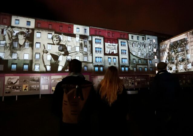 People stand in front of a projection on the former Stasi secret police headquarters in Berlin, Germany, November 4, 2019