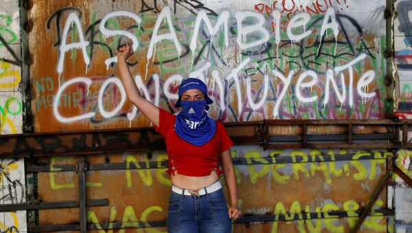 A demonstrator poses for a portrait in front of a graffiti reading Constituent Assembly during a protest against Chile's government in Santiago, Chile November 13, 2019. - Sputnik International