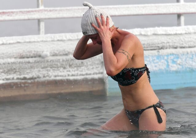 A woman during training for the open water swimming competitions in below 20 degrees Celsius in Krasnoyarsk
