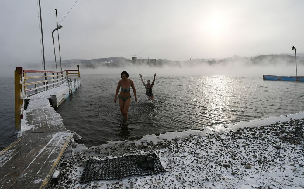 Women pose for photos during preparations for the cold water swimming competitions in the Yenisei River in Krasnoyarsk.Russian 'morzhi' ('walruses') say that cold water swimming has many health benefits.