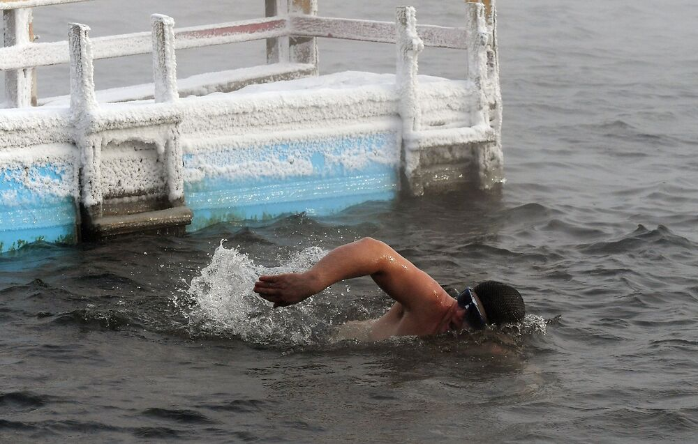 A man swims in the Yenisei River to prepare for the cold water swimming competitions in below 20 degrees Celsius temperature