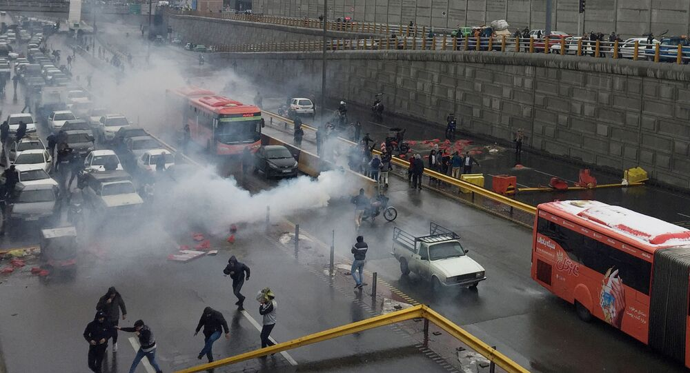 Riot police tries to disperse people as they protest on a highway against increased gas price in Tehran, Iran November 16, 2019