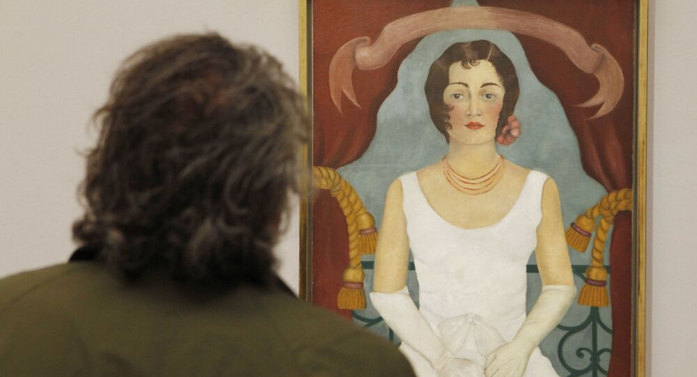 A visitor looks at a painting by Mexican artist Frida Kahlo titled Portrait of a lady in white during the opening of a show of her works on August 31, 2010 in Vienna