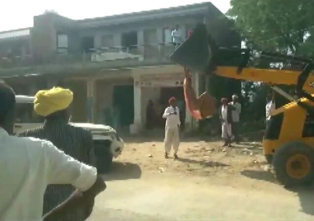 Rekha Devi, sarpanch of Mandawala village tries to climb a JCB machine in an attempt to stop anti-encroachment drive in Jalore, Rajasthan