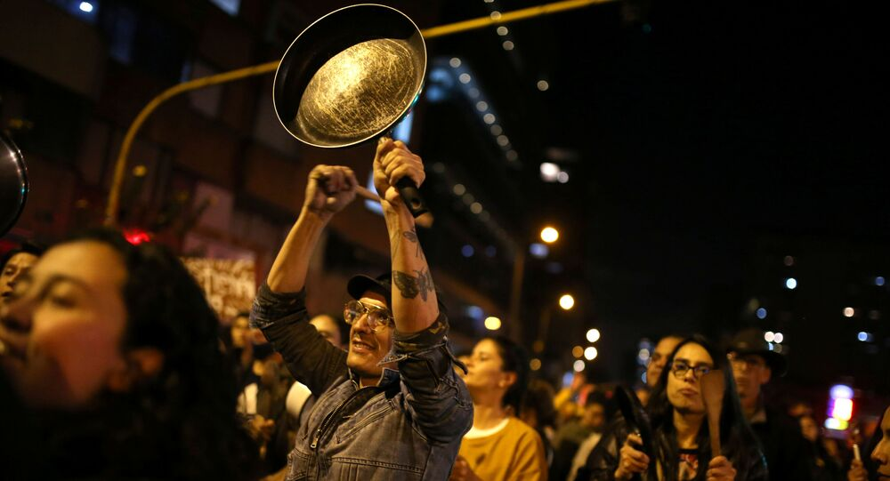 A demonstrator bangs a pan during a protest on the second day of a national strike, in Bogota, Colombia, 22 November 2019.
