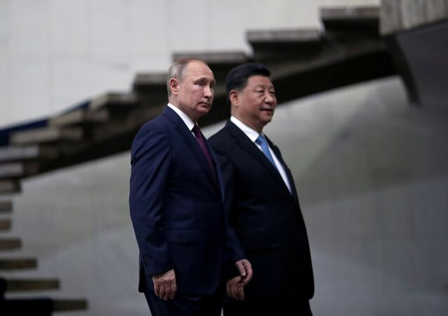 Russia's President Vladimir Putin and China's Xi Jinping walk down the stairs as they arrive for the BRICS summit in Brasilia, Brazil, 14 November 2019.