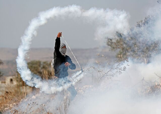 A Palestinian demonstrator returns a tear gas canister during a protest against Jewish settlements in Kofr Qadom, in the Israeli-occupied West Bank November 22, 2019