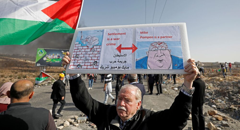 A demonstrator holds a sign during a protest as Palestinians call for a day of rage over U.S. decision on Jewish settlements, near the Jewish settlement of Beit El in the Israeli-occupied West Bank November 26, 2019.