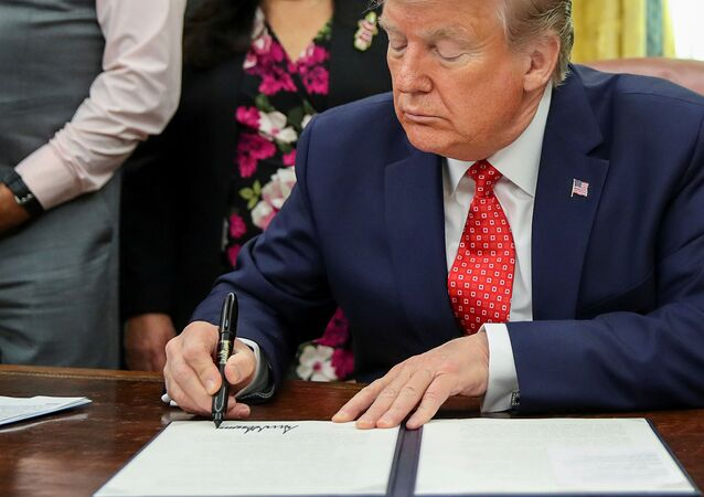 U.S. President Donald Trump signs an Executive Order to address the issue of missing and murdered Native Americans during a ceremony in the Oval Office at the White House in Washington, U.S. November 26, 2019.