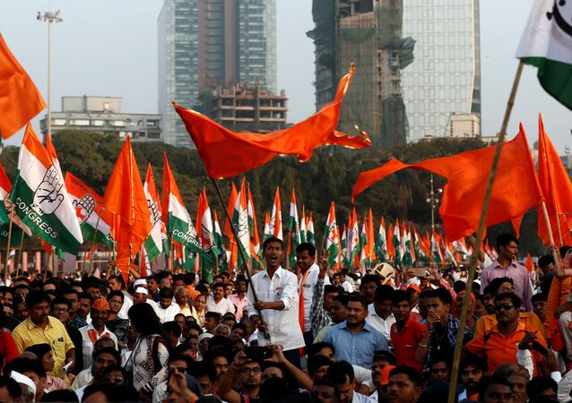 Supporters of Shiv Sena, Nationalist Congress Party (NCP) and the Congress party wave flags and shout slogans before the swearing-in ceremony of Shiv Sena party leader Uddhav Thackeray as chief minister of Maharashtra in Mumbai, India, November 28, 2019