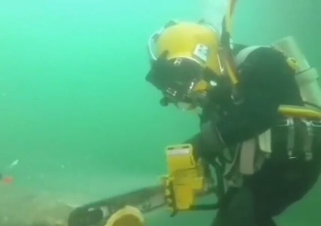 Man using a hydraulic chainsaw underwater