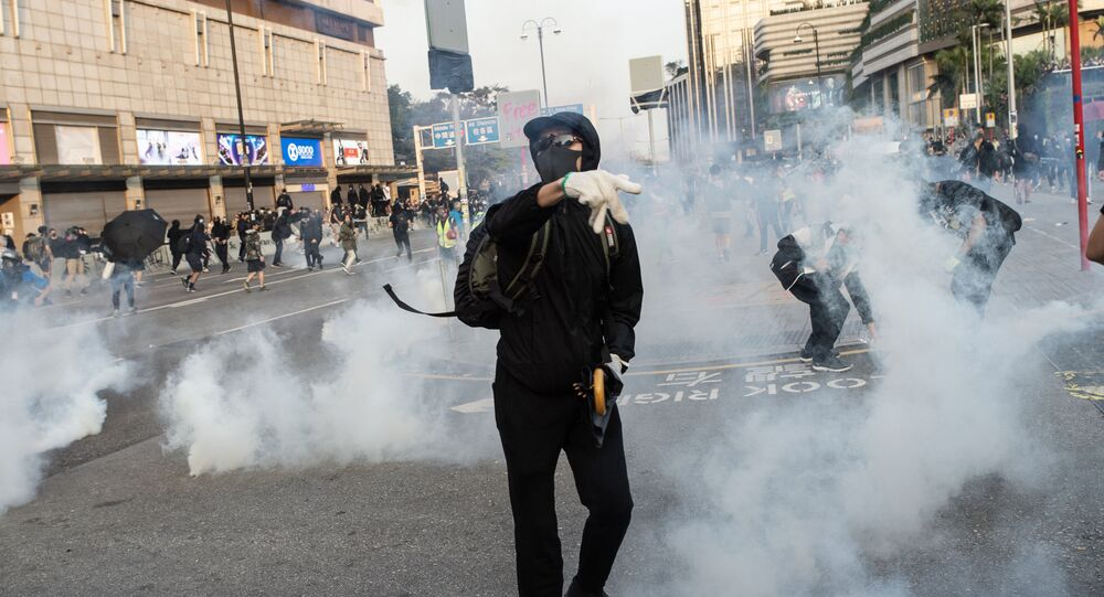 Pro-democracy protesters react after police fired tear gas during a march from the Tsim Sha Tsui district to Hung Hom in Hong Kong on December 1, 2019. - Tens of thousands of black-clad protesters flooded into the streets of Hong Kong on December 1, ending a brief election lull and demanding the government make concessions after pro-democracy candidates won a landslide victory.