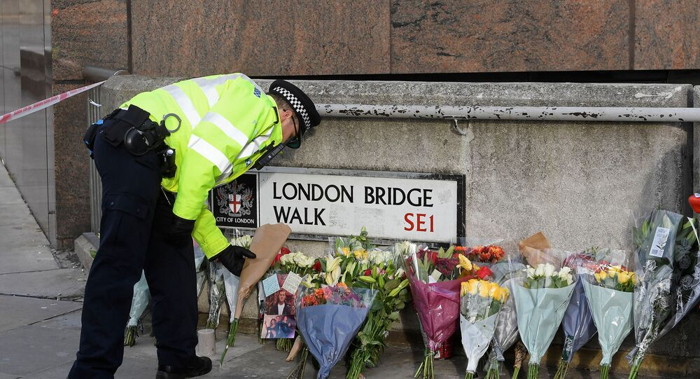 A police officer places a floral tribute near the scene of a stabbing on London Bridge, in London, Britain, December 1, 2019. REUTERS/Toby Melville