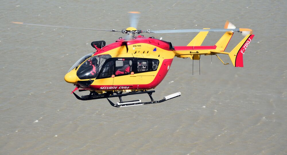 In this file photo taken on May 05, 2015 A French Civilian Security EC145 helicopter flies next to Mont-Saint-Michel in Normandy during a large air evacuation drill, in order to test coordination of air assets in the event of a potential crisis scenario at the site. - Three emergency workers were killed in a helicopter crash near Marseille while on a rescue mission in southern France where floods have left two dead, officials said December 2, 2019.