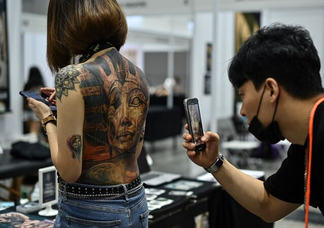 (FILES) In this file photo taken on November 29, 2019, a man takes pictures of a woman with tattoos during the International Malaysia Tattoo Expo in Kuala Lumpur