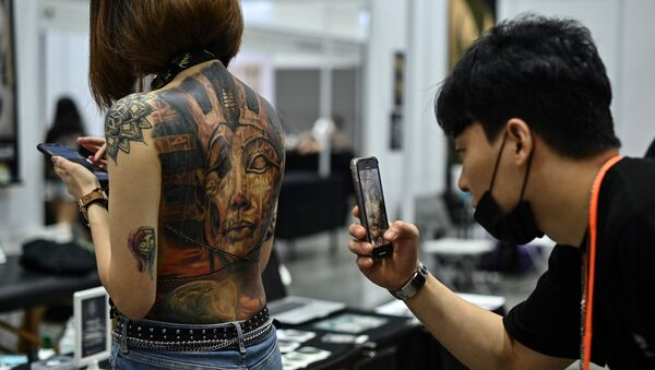 (FILES) In this file photo taken on November 29, 2019, a man takes pictures of a woman with tattoos during the International Malaysia Tattoo Expo in Kuala Lumpur - Sputnik International