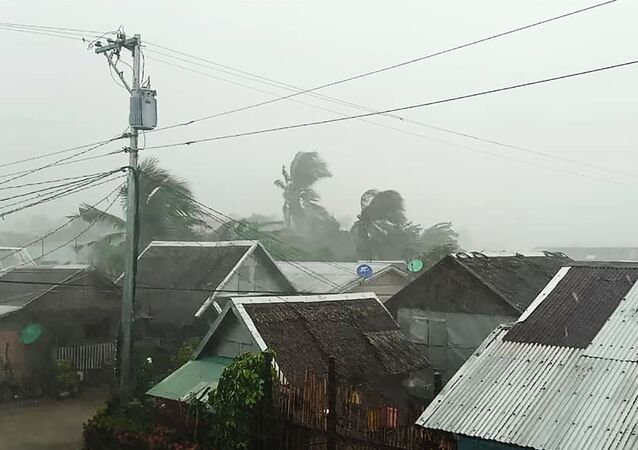 This handout image taken and received on December 2, 2019 courtesy of Gladys Vidal shows heavy rains and moderate wind from Typhoon Kammuri battering houses in Gamay town, Northern Samar province