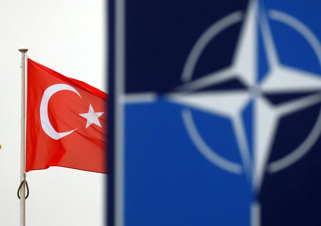 A Turkish flag flies next to NATO logo at the Alliance headquarters in Brussels, Belgium