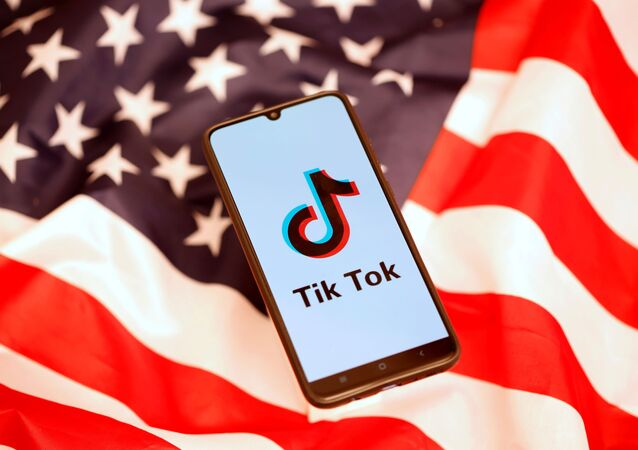 TikTok logo is displayed on the smartphone while standing on the U.S. flag