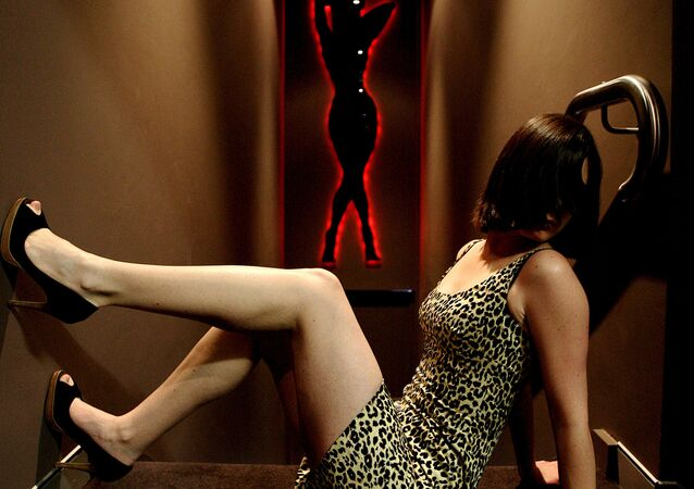 A sex worker sits in a passageway at the upmarket Xclusive brothel in Sydney's Bondi Junction on July 1, 2008