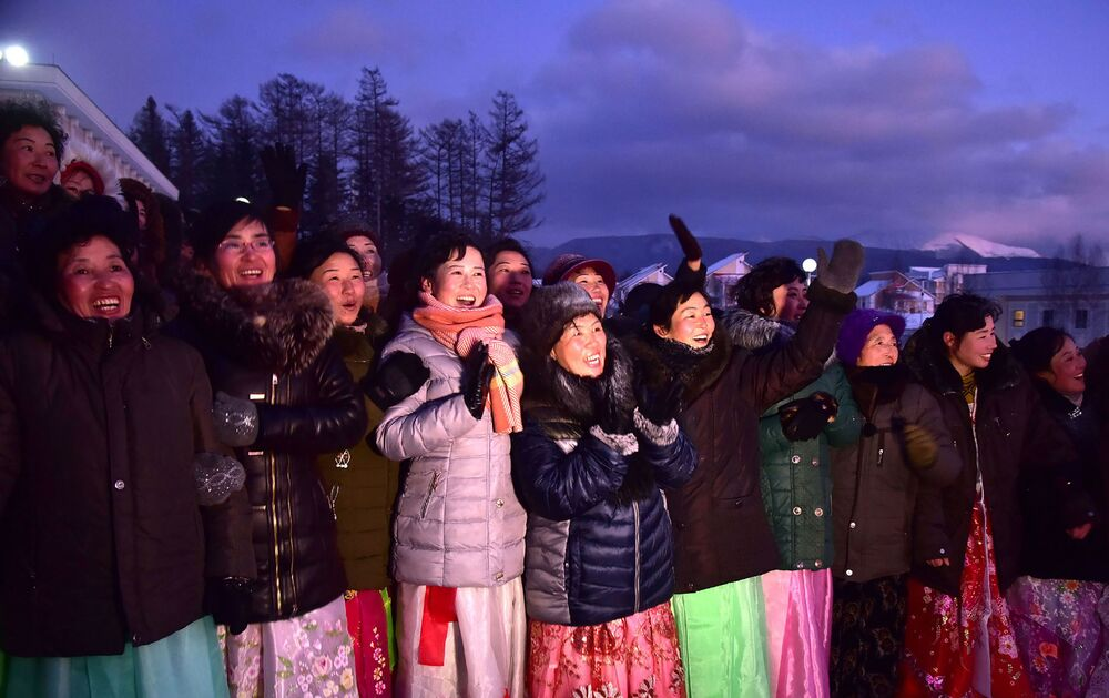 People cheer during a ceremony to mark the completion of the construction of the township of Samjiyon County.