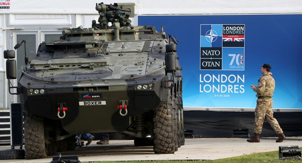 A soldier walks near an armoured vehicle ahead of a NATO leaders summit at the Grove in Watford, Britain December 3, 2019