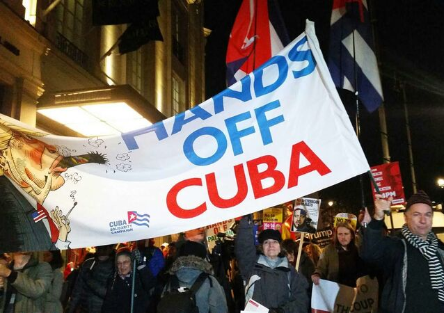 Rob Miller of Cuba Solidarity Campaign holds banner as anti-NATO demonstration moves from Trafalgar Sq to Buckingham Palace