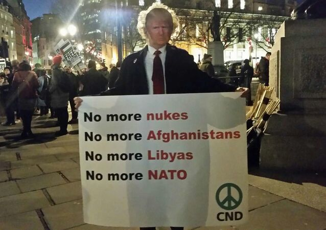 Man with Trump mask and sign opposed to nukes and war and NATO