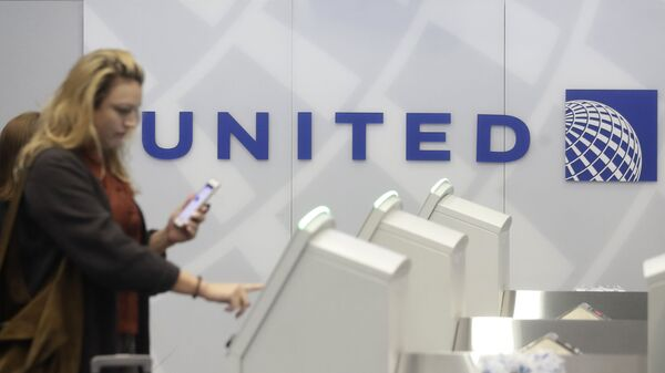 A woman uses a United Airlines kiosk at San Francisco International Airport in San Francisco, Tuesday, Nov. 26, 2019.  - Sputnik International