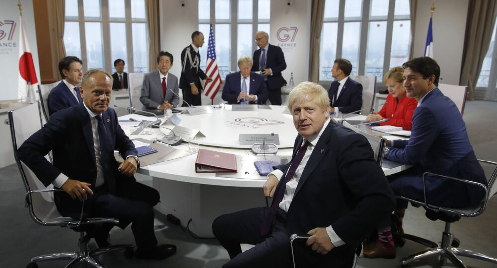 French President Emmanuel Macron, behind right, U.S. President Donald Trump, center behind, Japan's Prime Minister Shinzo Abe, partially hidden second right, Britain's Prime Minister Boris Johnson, right, German Chancellor Angela Merkel , third right, Canada's Prime Minister Justin Trudeau, right, Italy's Prime Minister Giuseppe Conte, left, and European Council President Donald Tusk attend a G7 working session on International Economy and Trade, and International Security Agenda during the G7 summit in Biarritz, southwestern France, Saturday Aug. 25, 2019.