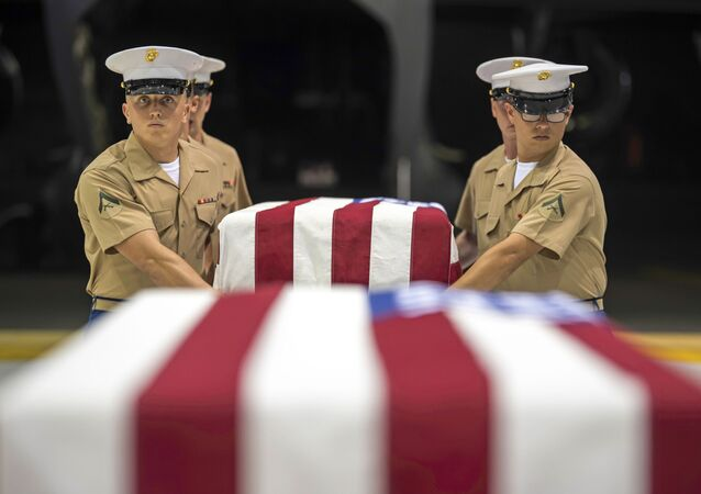 In this Wednesday, 17 July 2019 photo, US Marines carry transfer cases holding the possible remains of unidentified service members lost in the Battle of Tarawa during World War II, during what is known as an honourable carry conducted by the Defense POW/MIA Accounting Agency (DPAA), in a hangar at the Joint Base Pearl Harbor-Hickam in Hawaii.