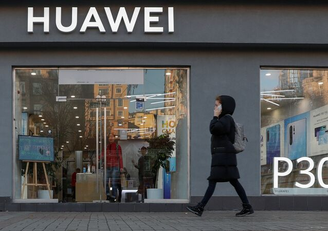 A woman speaks on her mobile phone as she walks past a Huawei store in central Kiev, Ukraine November 11, 2019.