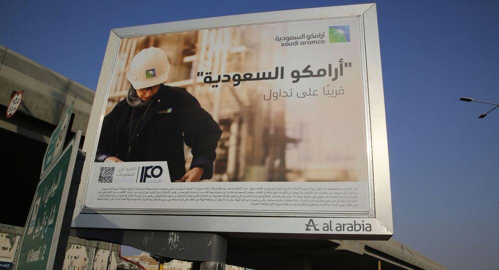 A man walks under a billboard displaying an advertisement for Saudi Arabia's state-owned oil giant Aramco with Arabic reading: Saudi Aramco, soon on stock exchange in Jiddah, Saudi Arabia, Tuesday, Nov. 12, 2019
