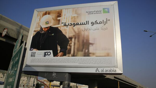 A man walks under a billboard displaying an advertisement for Saudi Arabia's state-owned oil giant Aramco with Arabic reading: Saudi Aramco, soon on stock exchange in Jiddah, Saudi Arabia, Tuesday, Nov. 12, 2019 - Sputnik International