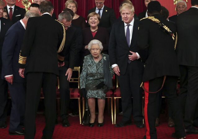 Britain's Queen Elizabeth II, centre, takes her seat with Britain's Prime Minister Boris Johnson and Chancellor of Germany Angela Merkel, behind, before a formal group photo during a formal reception for the heads of the NATO countries, at Buckingham palace in London Tuesday Dec. 3, 2019