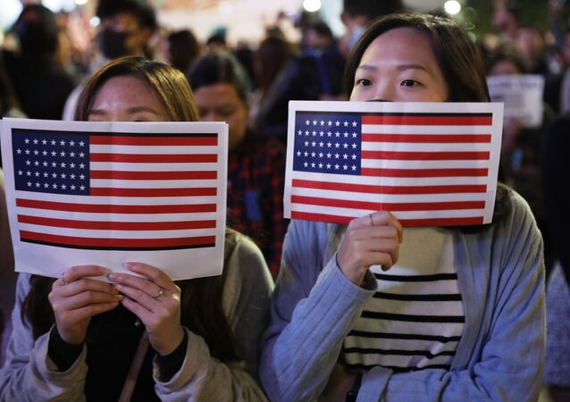 Protester holds U.S. flags during a demonstration in Hong Kong, Thursday, Nov. 28, 2019
