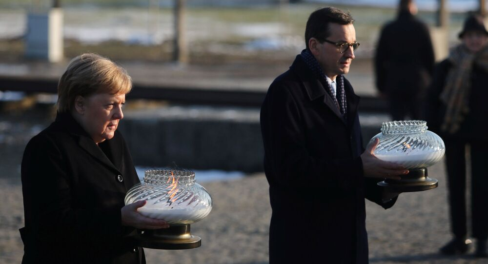 Polish Prime Minister Mateusz Morawiecki and German Chancellor Angela Merkel hold candles at the Monument to the Victims at the former Nazi German concentration and extermination camp Auschwitz II-Birkenau near Oswiecim, Poland December 6, 2019.