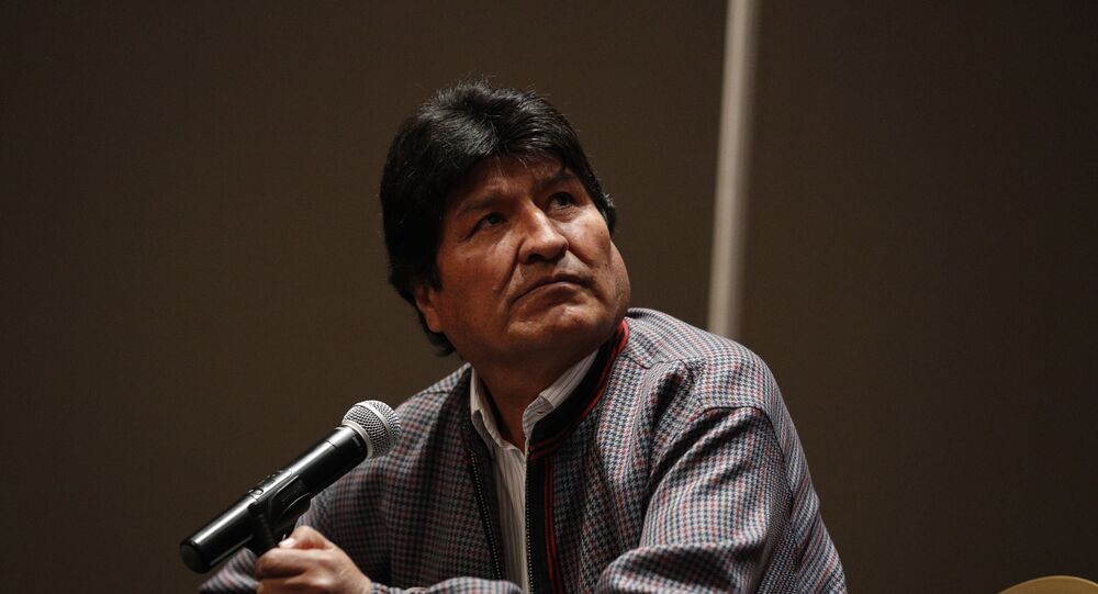 Former Bolivian President Evo Morales, who was granted asylum in Mexico, looks up toward a video playing on a screen during a press conference in Mexico City, Wednesday, Nov. 20, 2019.